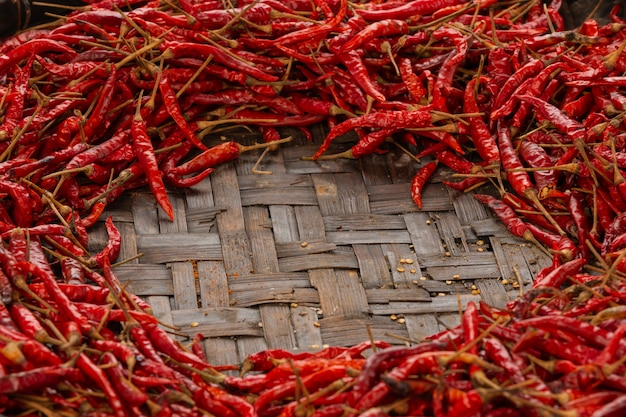 Red dried chilies placed on the space on the weave. Free Photo