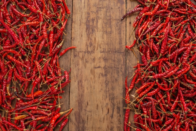 Red dried chilies that are stacked on the plank. Free Photo