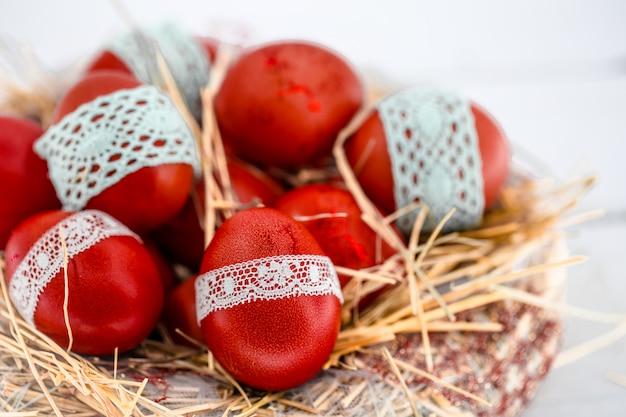干し草の巣に赤いイースターエッグ、レースリボン、クローズアップ、白い木の上に横たわってを結んだ 無料写真