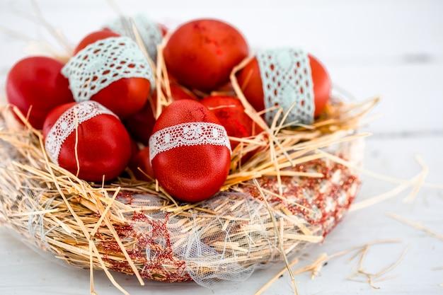 干し草の巣の赤いイースターエッグ Premium写真