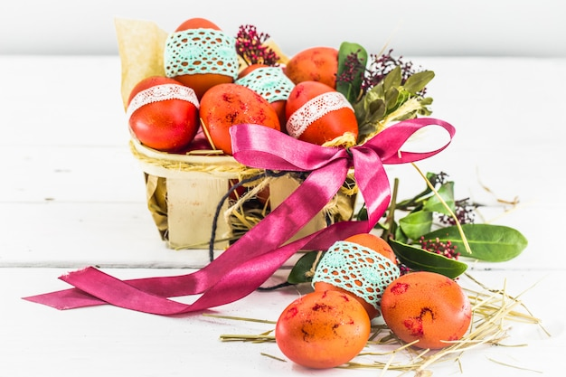 Красные яйца, перевязанные кружевной лентой, лежат в пасхальной корзинке с бантом Бесплатные Фотографии