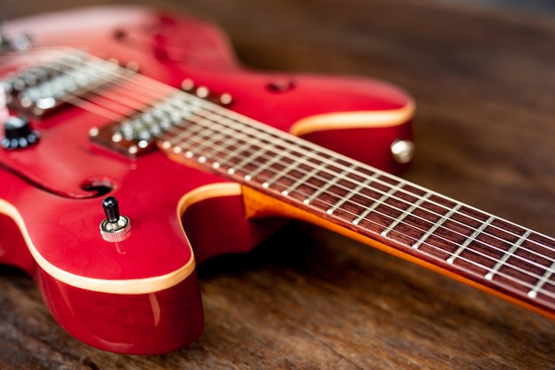 Red electric guitar on wooden floor Free Photo