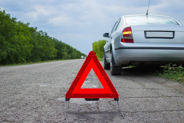 Red emergency stop sign and broken silver car on the road Premium Photo