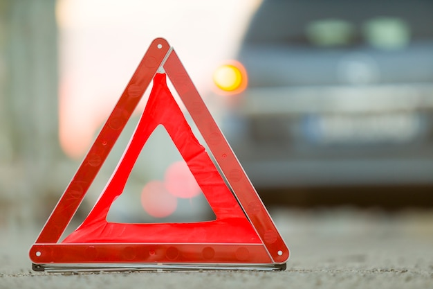 Red emergency triangle stop sign and broken car on a city street. Premium Photo