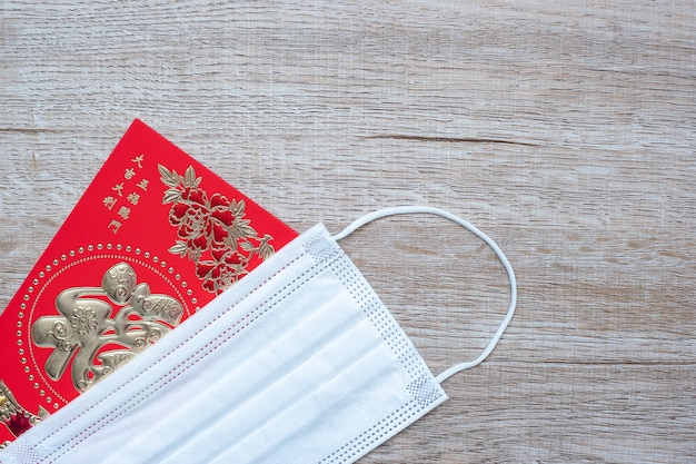 Red envelope or ang pao and medical face mask against coronavirus disease infection Premium Photo