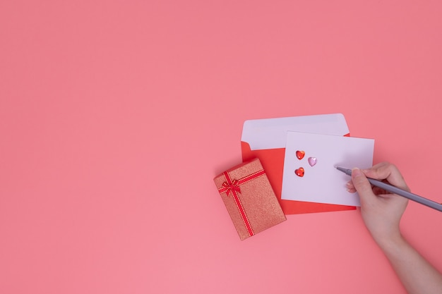 Red envelope and red gift box beside on pink Premium Photo