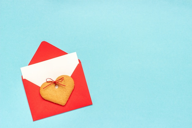 Red envelope with blank white card for text and heart shaped ginger cookies on blue background. Premium Photo
