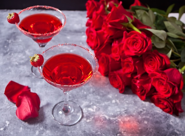 ロマンチックなディナーには、透明なガラスと赤いバラの赤いエキゾチックなアルコールカクテル。 Premium写真