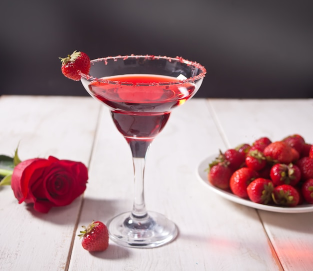 透明なガラスの赤いエキゾチックなアルコールカクテル、新鮮なイチゴとロマンチックなディナーの木製の白いテーブルに赤いバラのプレート。 Premium写真