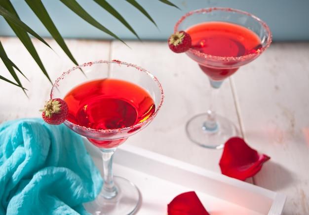 ロマンティックなディナーには、透明なグラスと木製の白いテーブルに赤いバラの花びらの赤いエキゾチックなアルコールカクテル。 Premium写真