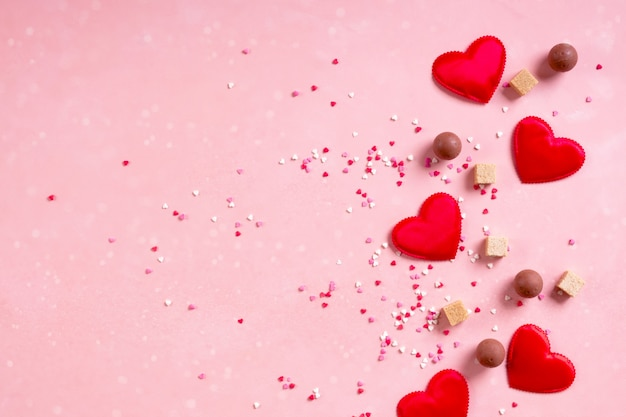 Red fabric hearts, sugar cubes, confetti, sweets candy chocolate on pink background. valentines day 14 february love minimal concept. flat lay, copy space, space for text, banner Premium Photo