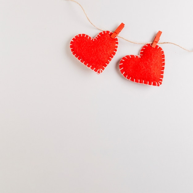 Red felt fabric hearts hanging on rope Free Photo