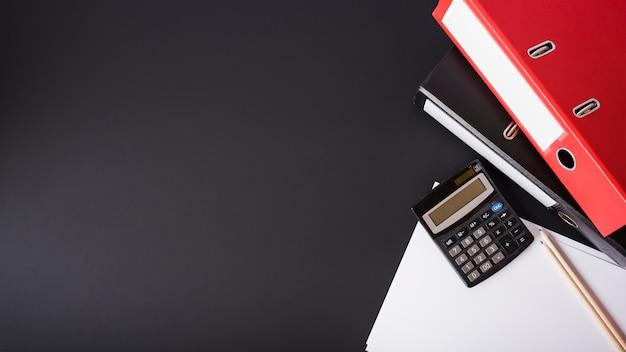Красный файл; калькулятор; карандаши и белые документы на черном фоне Premium Фотографии