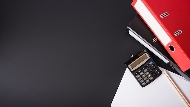 Red file; calculator; pencils and white papers on black background Free Photo