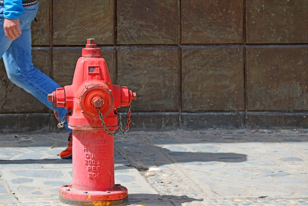 Red fire extinguisher on the footpath with a man walking behind, puno old town, peru, south america Premium Photo