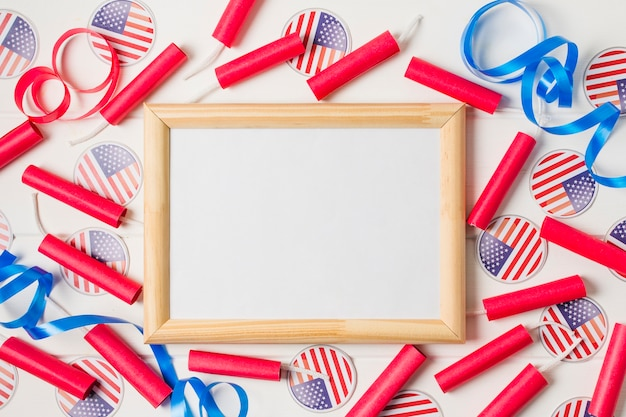 Red firecrackers; ribbon and usa flag badges around the blank wooden white board Free Photo
