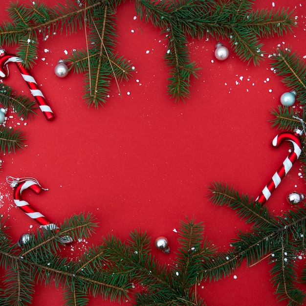 Red flat lay minimalistic christmas square banner with fir branches and candies, christmas tree and toys. Premium Photo