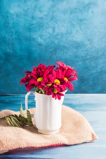 Red flowers in jug on canvas Free Photo