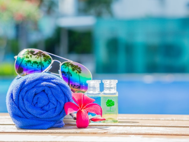Red flowers, sunglasses, shampoo, lotion and rolled up towels at the side of swimming pool Premium Photo
