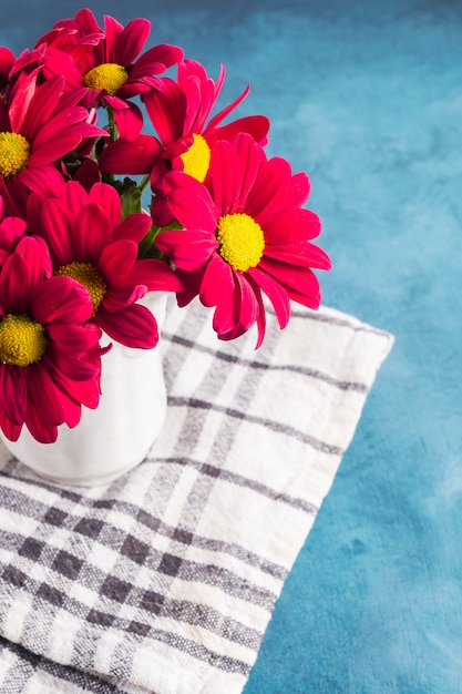 Red flowers in vase on cloth Free Photo