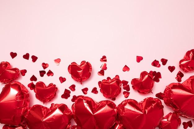 パステルピンクの背景にハート形の赤い箔風船。バレンタインの休日のお祝いや結婚式パーティーの装飾背景 Premium写真