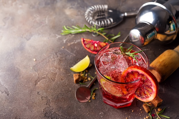Red fresh colorful exotic alcoholic cocktail with orange and ice on a stone background. Premium Photo