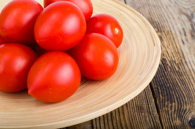 Red fresh tomatoes on wooden background Premium Photo