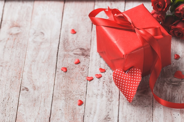 Red gift box on a wooden table with a heart next to it for Table o present libramont