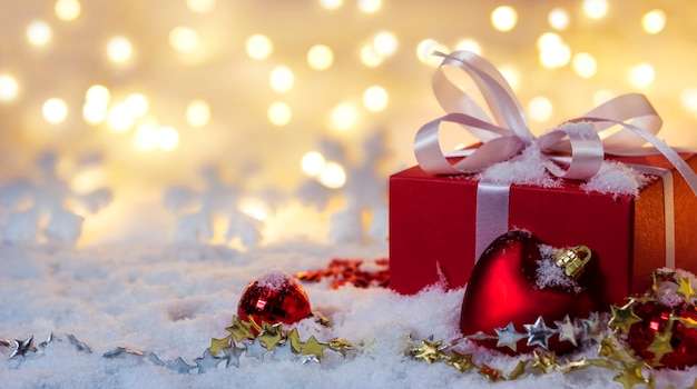 Red gift box on snow with bokeh background Premium Photo