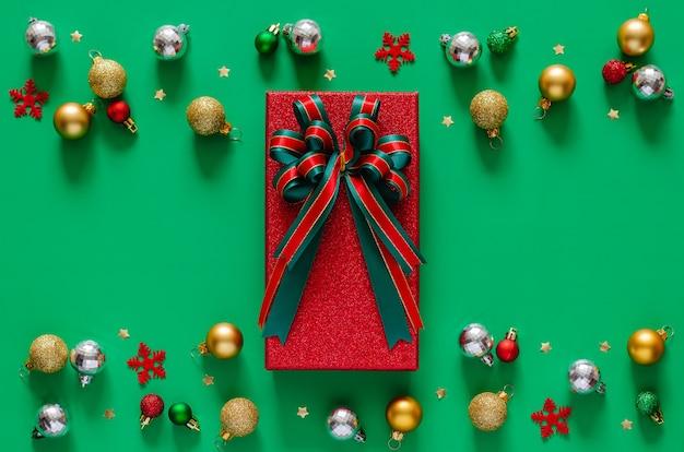 Красная подарочная коробка с лентой банта и рождественскими украшениями безделушек на зеленом фоне. Premium Фотографии