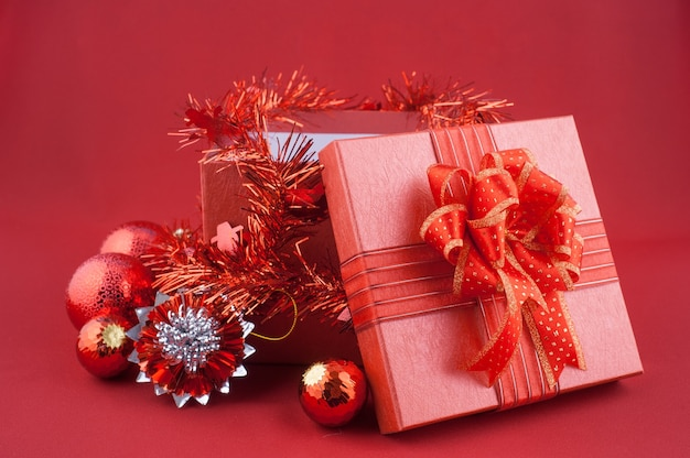 Red Gift Box with Decorations on Red background. Christmas Holiday Concept Premium Photo