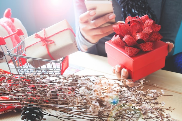 Red gift box on woman hand, using mobile phone. holiday concept Premium Photo