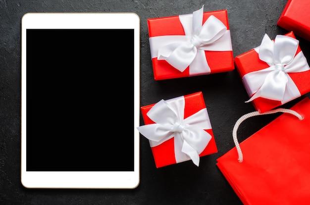 빨간색 선물 상자와 텍스트에 대 한 빈 화면 태블릿. 공간을 복사하십시오. 프리미엄 사진
