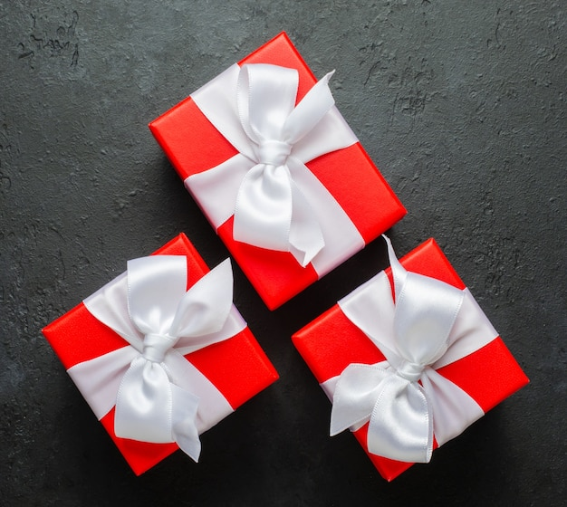 흰색 리본이 달린 빨간색 선물 상자입니다. 검은 콘크리트 배경. 공간을 복사하십시오. 프리미엄 사진