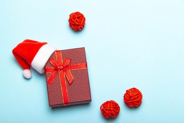 青い背景に赤い贈り物。サンタの帽子をかぶったプレゼント。クリスマスと新年。休日への贈り物。赤いギフト包装。青い背景 Premium写真