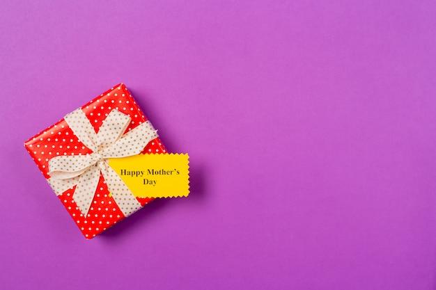 グリーティングカードとテキスト紫色の背景に幸せな女性の日と赤いギフトプレゼントボックス。フリースペース。テキストのスペースをコピーします。母の日のコンセプトです。フラット横たわっていた。上面図。 Premium写真