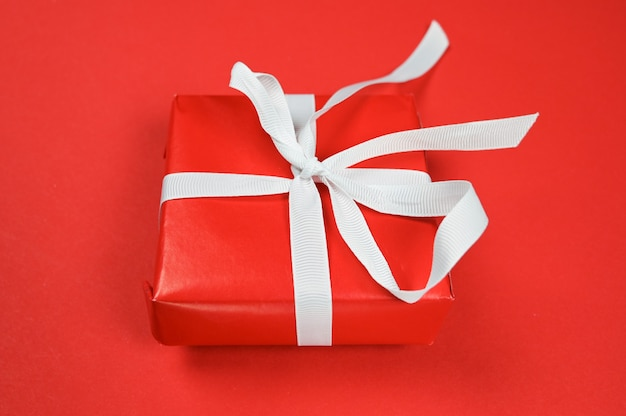 Красный подарок с белой лентой на красной поверхности. Premium Фотографии