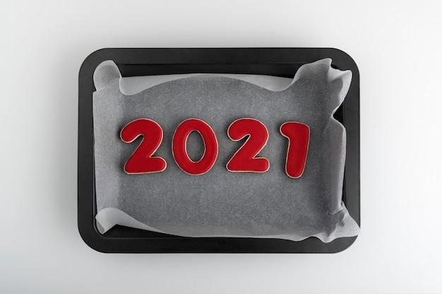天板に赤いジンジャーブレッドクッキー2021。新年のクッキー。 Premium写真