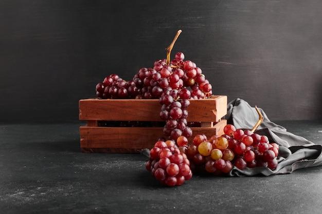 赤いブドウは黒い表面の木製トレイに束ねられます。 無料写真