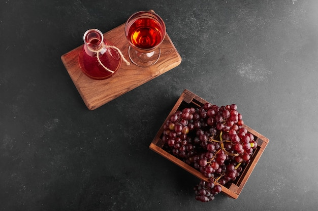 ワインのグラス、上面図と木製のトレイに赤ブドウの房。 無料写真