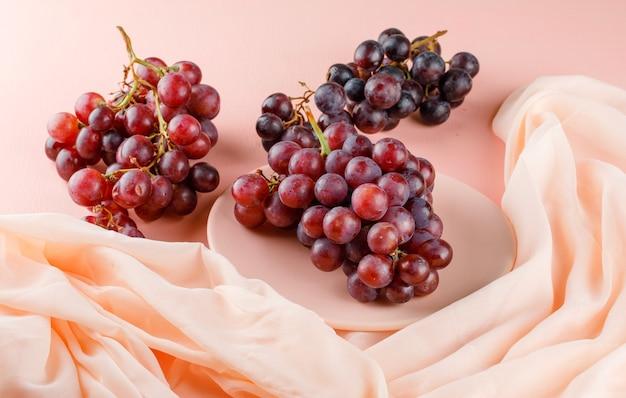 Красный виноград в тарелке на розовом и текстиле. высокий угол обзора. Бесплатные Фотографии