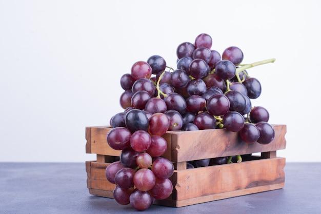Красный виноград в деревянном подносе на синей поверхности Бесплатные Фотографии