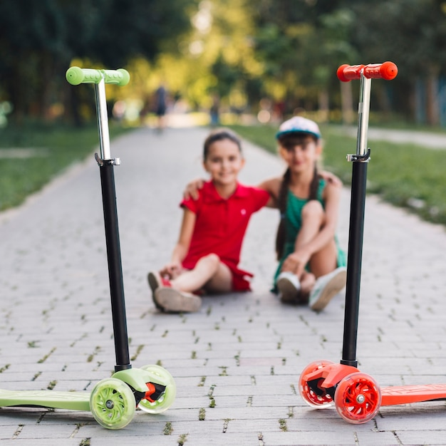Red and green kick scooters in front of two girls sitting together on walkway Free Photo