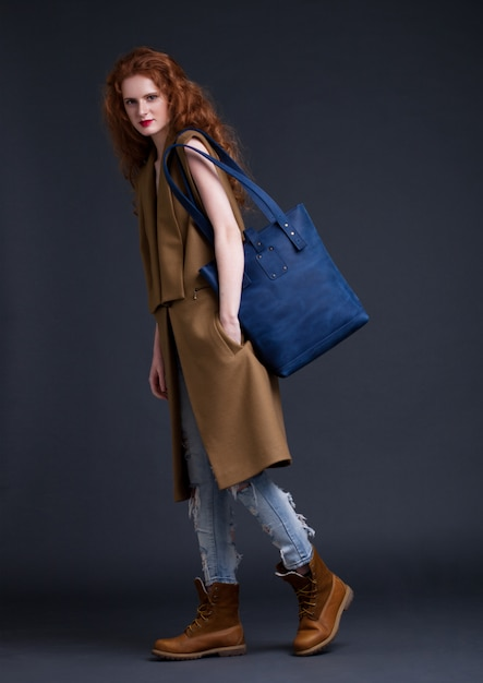 Red hair fashion model holding large blue leather bag on dark background. girl wearing long sleeveless jacket with jeans and boots. Premium Photo