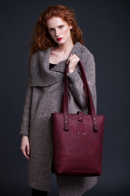 Red hair fashion model holding large dark red leather bag on dark background. girl wearing long jumper. Premium Photo