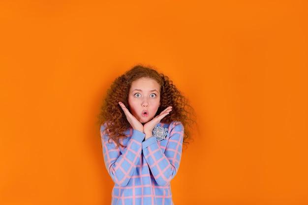 놀란 오렌지 배경에 빨간 머리와 곱슬 머리 소녀 프리미엄 사진