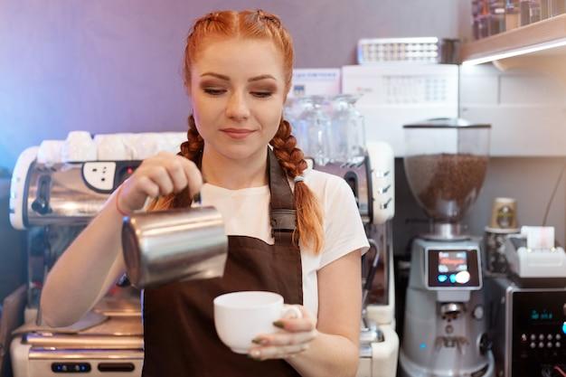 Рыжая девушка-бариста варит кофе из турка в кофейне Premium Фотографии