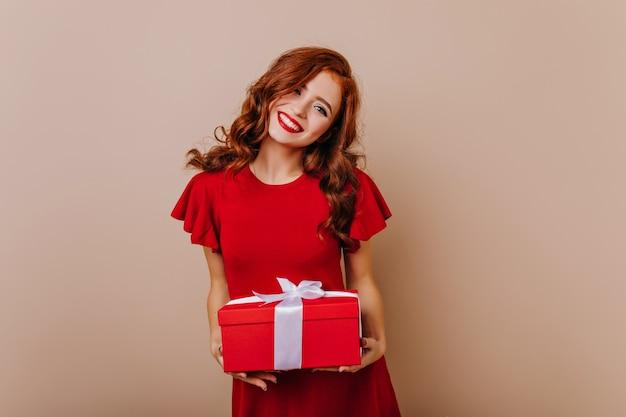 Рыжая именинница улыбается привлекательная женская модель в красном платье, держа рождественский подарок. Бесплатные Фотографии