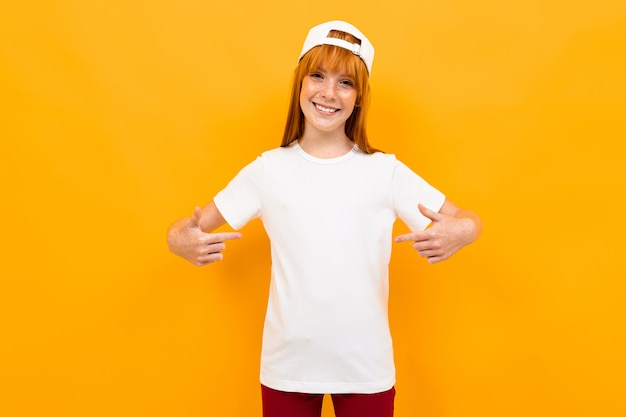 Red-haired charming girl in a white t-shirt on a  of an orange wall, points her fingers to herself, mock-up Premium Photo