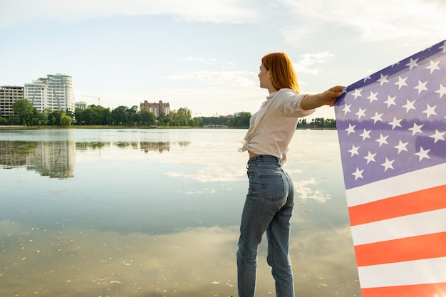 Red haired girl holding usa national flag in her hands. positive young woman celebrating united stat